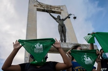 Activists raise green headscarves during a demonstration demanding the legalisation of abortion at the Constitution Square in…