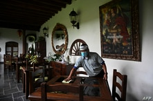 A man cleans a table in the restaurant area of a hotel in Antigua Guatemala, Sacatepequez Departament, 45 km southeast of…