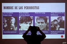 A member of a human rights organization takes a picture of a screen depicting four Dutch journalists killed by the Salvadoran…