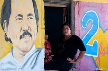 A woman sits next to an image of Nicaragua's President Daniel Ortega in Catarina, Nicaragua October 1, 2020.REUTERS/Oswaldo…