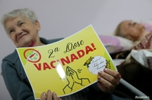"""An elderly citizen holds a cardboard, that reads: """"Second dose. Vaccinated!"""" after receiving her second dose of Sinovac's…"""