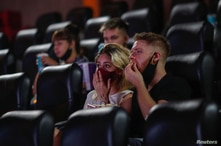 People wearing protective face masks are seen inside a movie theater, as cinemas in Argentina reopen amid an easing of new…