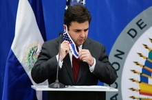 U.S. President Joe Biden's special envoy for the Northern Triangle Ricardo Zuniga takes off his face mask during a news…