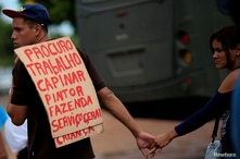 A Venezuelan migrant carries a placard to apply for a job near a makeshift camp at Simon Bolivar square in Boa Vista, Brazil…