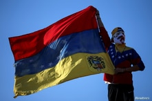 A man using a Guy Fawkes mask shows the Venezuelan flag during a demonstration in support of Venezuela's opposition leader Juan…