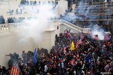 FILE PHOTO: Police release tear gas into a crowd of pro-Trump protesters during clashes at a rally to contest the certification…