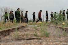 Central American migrants wait to be transported by the U.S. Border Patrol after crossing the Rio Grande river into the United…