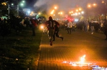 Demonstrators run while tear gas falls during a protest demanding government action to tackle poverty, police violence and…