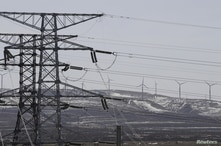 FILE PHOTO: FILE PHOTO: Power lines and wind turbines are pictured at a wind and solar energy storage and transmission power…