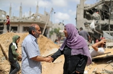 Palestinians shake hands after returning to their destroyed houses following Israel- Hamas truce, in Beit Hanoun in the…