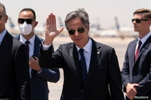 U.S. Secretary of State Antony Blinken waves as he steps off his plane upon arrival at Cairo International Airport, in Cairo,…