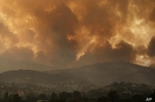 ILE - In this Friday, Aug. 6, 2021 file photo, smoke spreads over Parnitha mountain during a wildfire in the village of Ippokratios Politia, Greece, about 35 kilometres (21 miles), north of Athens. Thousands of people fled wildfires burning out of control in Greece and Turkey on Friday, as a protracted heat wave left forests tinder-dry and flames threatened populated areas and electricity installations. (AP Photo/Lefteris Pitarakis)