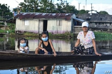 A woman and two girls wearing face masks, as a preventive measure against the spread of the novel coronavirus, COVID-19, sail…