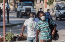 (FILES) In this file photo two men wear masks as they walk in the streets of downtown Port-au-Prince on March 26, 2020. - When…