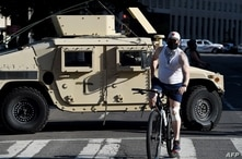 A man rides his bike past a National Guards armored vehicle near the White House as demonstrators gather to protest the killing…
