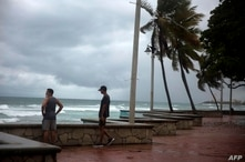 Men look at the sea during the Isaias storm in Santo Domingo, on July 30, 2020. (Photo by Erika SANTELICES / AFP)