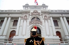 This handout picture released by the Peruvian Presidency shows a husar at guard at the doors of the Congress,  where President…