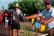 Men offer gasoline for sale on the streets of Maracaibo, Zulia State, Venezuela, on August 25, 2020, amid the COVID-19…