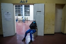 A poll worker sits as she wait for voters to arrive at a polling station in a school in Caracas, on December 6, 2020 during the…