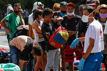 Venezuelan migrants wear a face masks as they queue to receive food and medicines from members of the Red Cross on a highway in…