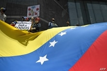"""Activists hold a sign reading """"Vaccines for all"""" and a giant Venezuelan flag during a protest to demand all healthcare workers…"""