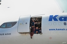 Afghan people climb up on a plane and sit by the door as they wait at the Kabul airport in Kabul on August 16, 2021, after a…