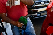 A worker pumps gas into a vehicle at a state oil company PDVSA gas station in Caracas, Venezuela, Friday, Jan. 3, 2020. Oil…