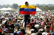 FILE - In this Feb. 22, 2019 file photo, a child holds a Venezuelan flag during the Venezuela Aid Live concert on the Colombian…