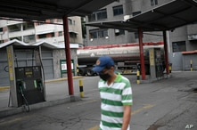 A man wearing a face mask amid the new coronavirus pandemic walks in front of an empty state oil company gas station while a…