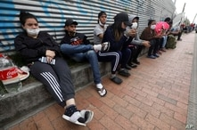 In this April 30, 2020 photo, Venezuelan migrants wait for buses that will transport them to the Venezuelan border, in Bogota,…