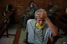 A man, equipped with a protective face mask as a precaution against the spread of the new coronavirus, waits to receive a free…