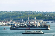 A Washington state ferry passes a Hong-Kong based Orient Overseas Container Line cargo container ship entering the Port of…