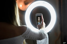 In this Feb. 28, 2018 photo, Matty Nev Luby holds up her phone in front of a ring light she uses to lip-sync with the…