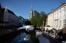 Two pigeons fly across a canal in Bruges, Belgium, during a partial lifting of a lockdown to prevent the spread of coronavirus,…