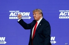 President Donald Trump gives a fist pump to the crowd after speaking at the Students for Trump conference at Dream City Church,…