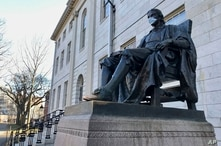The John Harvard statue at Harvard University, a popular tourist attraction at the campus in Cambridge, Mass, sits adorned with…