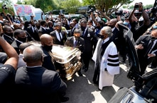 The Funeral home team pushes the casket of George Floyd into the hearse as the Rev. Al Sharpton, right, looks on after the…