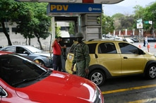 A soldier stands guard at a PDVSA state oil company gas station where drivers wait in line for hours  to fill up in Caracas,…