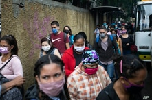 Pedestrians and commuters wearing face masks amid the new coronavirus pandemic crowd a sidewalk near a bus stop in Caracas,…
