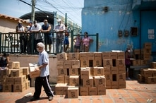 Residents help to unload and stack boxes of basic food staples, such as pasta, sugar and flour, provided by a government food…