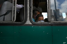 A child wearing a protective face mask looks out a window as he travels on a bus in Caracas, Venezuela, Saturday, June 6, 2020…