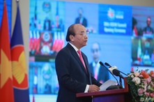 Vietnamese Prime Minister Nguyen Xuan Phuc delivers a speech in front of a TV screen showing ASEAN leaders at the opening…