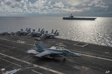 In this photo provided by U.S. Navy,  an F/A-18E Super Hornet lands on the flight deck of the USS Ronald Reagan (CVN 76), as…