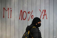 A woamn walks past graffiti against the Pension Fund Administrators, AFP, system in Santiago, Chile, Wednesday, July 22, 2020…