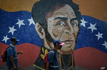 Men wearing masks against the spread of the new coronavirus, walk past a mural with the image of Venezuelan independence hero…