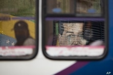 A mural of President Nicolas Maduro is framed by a window of a public bus driving past in Caracas, Venezuela, Wednesday, July…