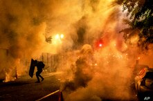 A Black Lives Matter protester uses a shield as federal officers use chemical irritants to disperse demonstrators at the Mark O…