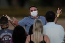Brazil's President Jair Bolsonaro, who is infected with COVID-19, wears a protective face mask as he talks with supporters…