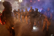 Federal officers advance on a group of demonstrators during a Black Lives Matter protest at the Mark O. Hatfield United States…