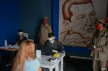 Members of the Venezuelan Electoral Council, sitting, wear face masks and shields amid the spread of the new coronavirus at a…